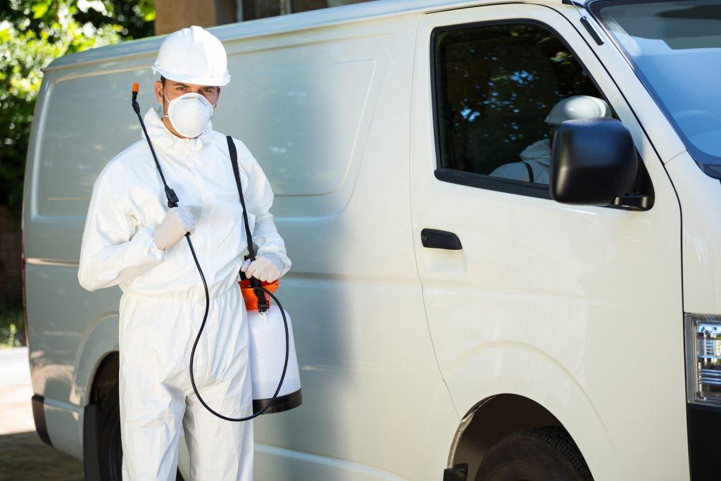 Portrait of pest control man standing next to a van